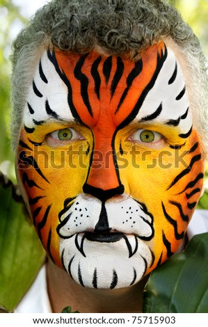 A man with piercing eyes, painted like a tiger. - stock photo