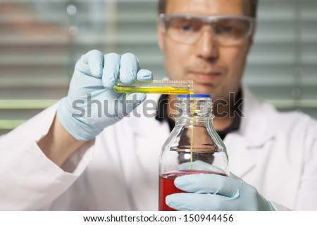 A man with red and yellow liquid in a laboratory - stock photo