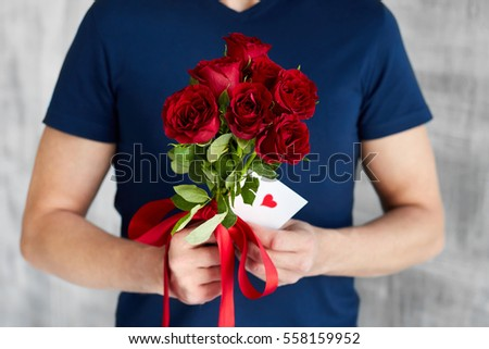 a man with red roses and valentine in the hands. valentine day love beautiful