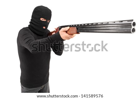 A man with robbery mask attacking someone with shotgun isolated on white background - stock photo