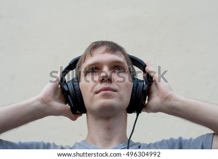 A man with two hands presses the headphones on your ears.