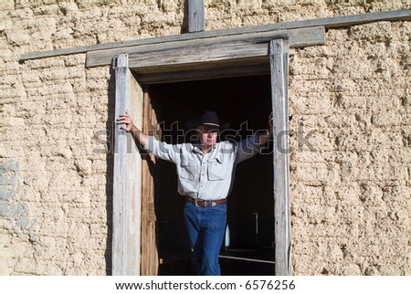 A man with wearing a cowboy hat standing in the door of an old weathered adobe building. - stock photo