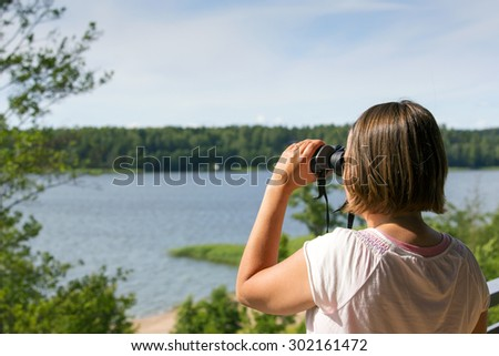 A man/woman is watching birds and scenery with binoculars from high above the ground. Image is taken against a lake or sea on a sunny day. - stock photo