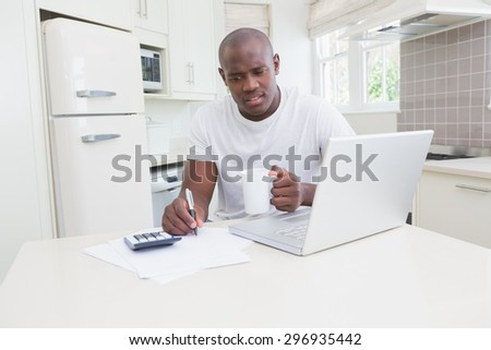 A man working and using his laptop in the kitchen