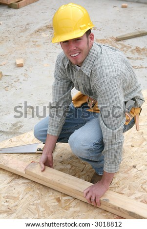 A man working building a home and cutting some wood