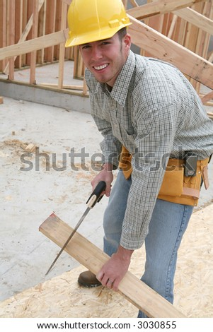 A man working building a home and cutting some wood - stock photo