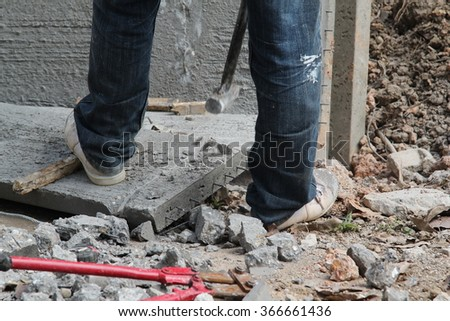 A man working hitting concrete block with sledge hammer in construction site. - stock photo