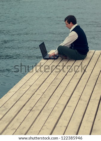 A man working on a laptop at the sea. Young businessman with a computer outdoors. - stock photo