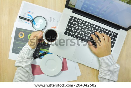 A man working on a wooden desk with a laptop.