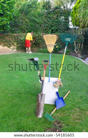 A man works in his yard trimming shrubbry and conducting lawn care - stock photo