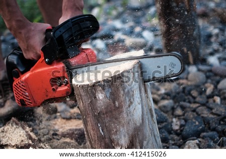 A man works in the forest holding chain saw, ripping the wood block, the chips fly apart - stock photo