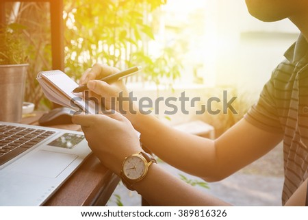 A man writing on notepad at morning time. - stock photo