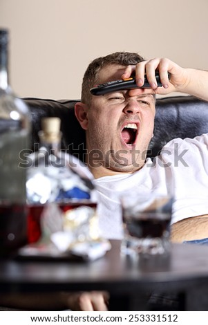 A man yawns watching TV - stock photo
