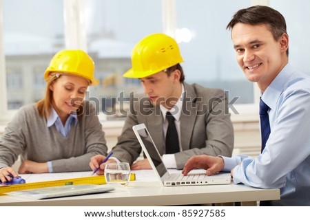 A manager working with laptop, looking at camera and smiling against his colleagues - stock photo
