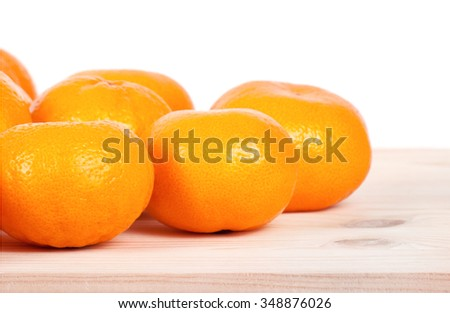 A mandarin on wooden table. Empty copy space for editor's text.