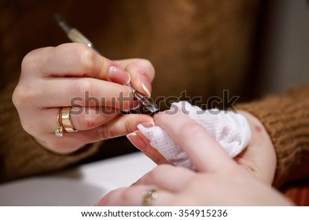a manicure master is doing manicure to her client