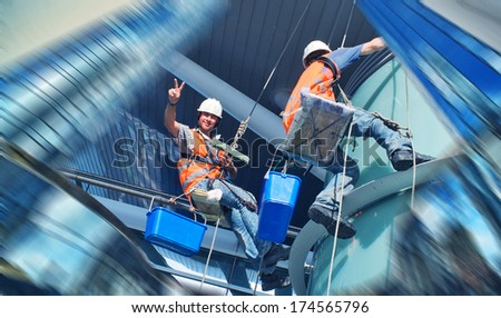 A mans cleaning windows on a high rise building - stock photo