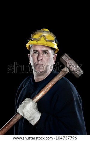 A manual laborer with a sledgehammer wearing a yellow hardhat and protective work gloves isolated on black - stock photo