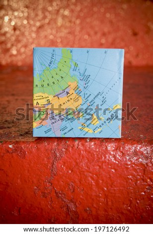A map of the world laying on a red stone background. - stock photo
