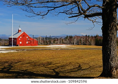 A Maple tree and flagpole frams a small red barn sits on the edge of a field partially covered with melting snow on a warm spring day in Vermont with a scenic view of the White Mtns in the distance. - stock photo