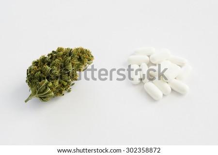 A marijuana bud next to a bunch of prescription pills - stock photo