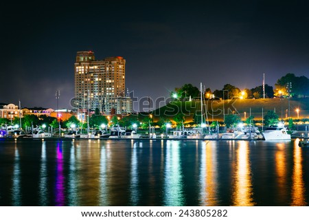 A marina and Federal Hill at night at the Inner Harbor in Baltimore, Maryland. - stock photo