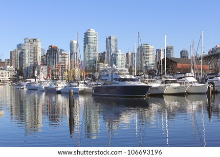 A marina in Vancouver's trendy False Creek/False Creek Marina/High end recreational boats are moored in a Vancouver marina. - stock photo