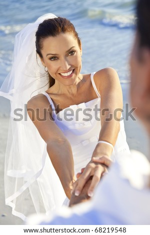 A married couple, bride and groom, together holding hands laughing and having fun in sunshine on a beautiful tropical beach