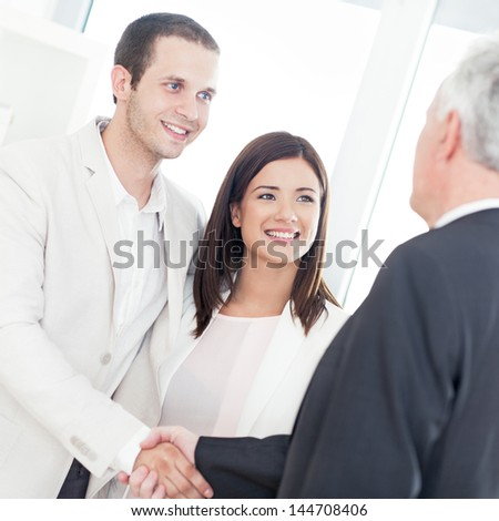 A married couple shaking hands with their financial advisor. - stock photo