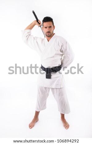 a martial arts man wielding a sword. Focus on the sword. - stock photo