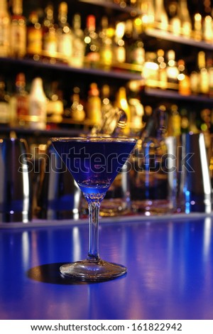 A martini glass on a purple bar. - stock photo