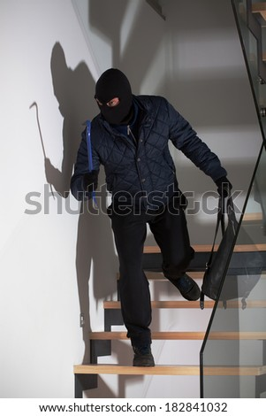 A masked burglar lying in wait for his victim on the stairs - stock photo