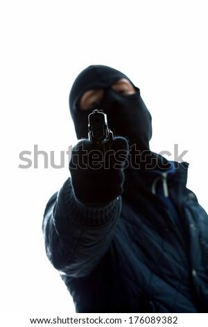 A masked man holding a gun aimed at us - stock photo