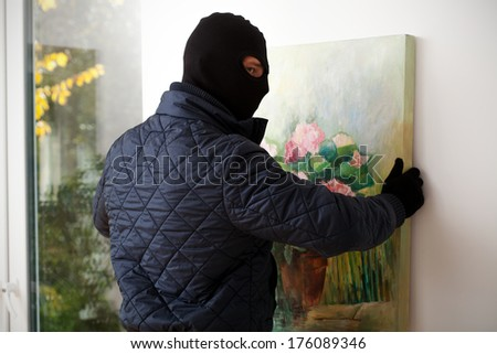 A masked man trying to take a painting off the wall - stock photo