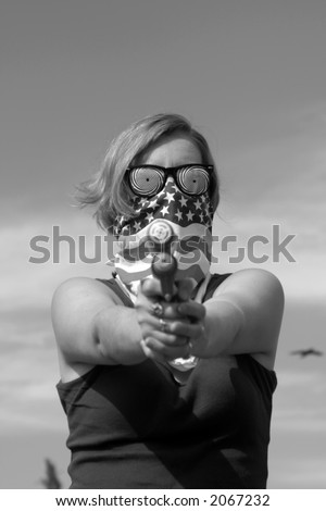 a masked young blondie woman points a squirt gun directly at YOU in black and white