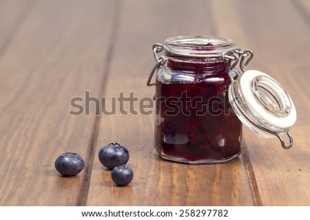 A mason jar with blueberry jam on a wooden table. Vintage style. - stock photo