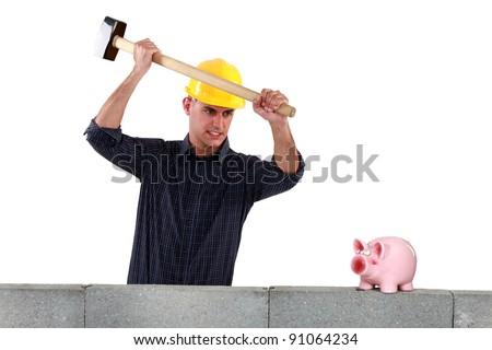 A mason smashing his piggy bank. - stock photo