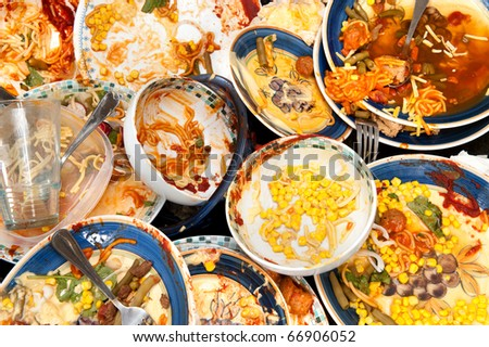 A mass of dirty, filthy dishes with food scraps waiting to be washed. - stock photo