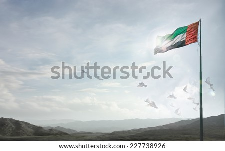 A massive flag of UAE flying against a horizon of Hajjar mountains, Fujeirah, UAE. - stock photo