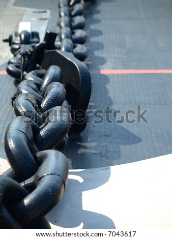 A massive metal chain on the deck of a naval ship (shallow DOF) - stock photo