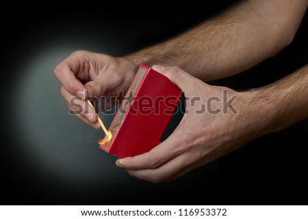 A Match ignited by rubbing the match head against a match box. - stock photo