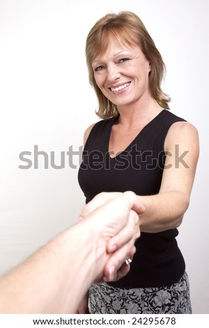 A mature adult female shaking hands with a person off camera. - stock photo