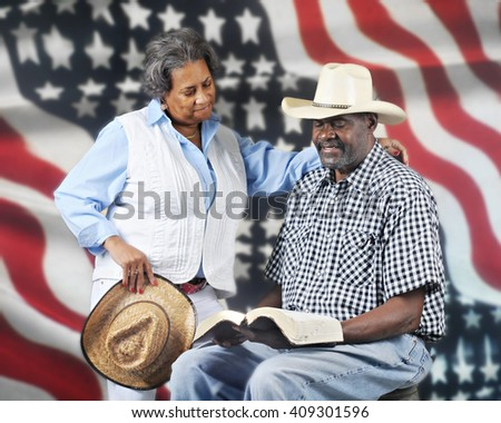 A mature African American cowboy couple reading the Bible with a stars and stripes background. - stock photo
