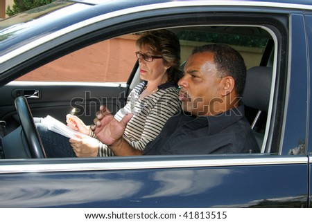 a mature African - American man having a driving test and being stressed out by the tester - stock photo