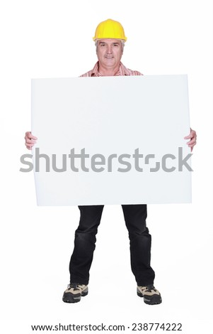 A mature architect holding a blank poster. - stock photo