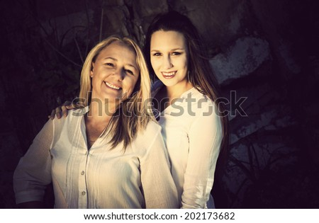 A mature blonde mother is posing with her beautiful Greek looking daughter on the banks of the river in South Africa. Their love and family values shine through. - stock photo