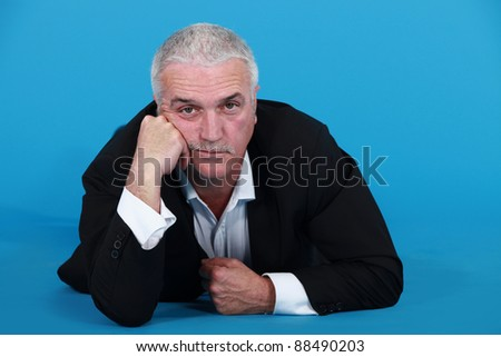 A mature bored businessman laying on the floor. - stock photo