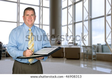 A mature business man taking notes in a large lobby - stock photo