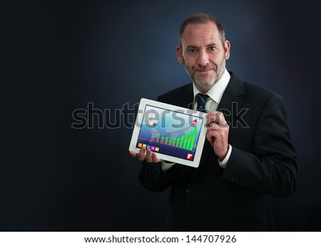 a mature businessman or salesman shows his Tablet PC with positive chart - stock photo