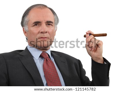 A mature businessman smoking a cigar. - stock photo